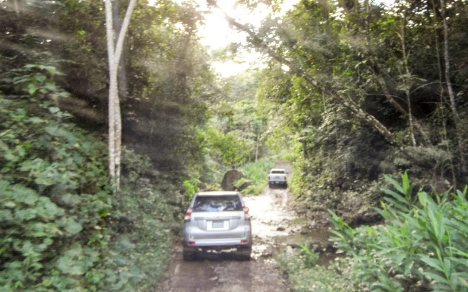 "Low light, dirty windshield, bouncing car: almost works. Our ""caravana"" crossing another stream to get to one more finca before the sun sets. Near San Sebastián de Yalí, Jinotega."